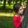 Little smiling girl hiding behind tree — Stock Photo #58672965