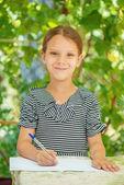 Petite fille belle écrit dans Carnet — Photo