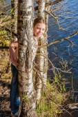 Little girl hides among birch trees — Stock Photo