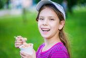 Little smiling girl holding an ice cream — Stock Photo