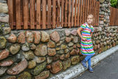 Little girl fun at stone fence — Stock Photo