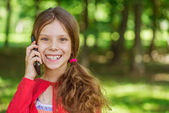 Little girl talks by mobile phone — Stock Photo