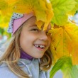 Little girl in yellow coat collects yellow maple leaves — Stock Photo #59140963