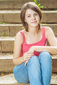Young girl sits on steps — Stock Photo