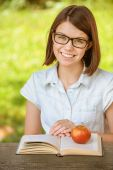 Portrait young pretty girl glasses with book and apple — Stock Photo
