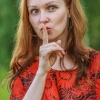 Woman in red dress put finger to lips — Stock Photo #59933695