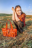 Woman with red bag sits in field — Stock Photo