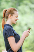 Smiling young woman talking on mobile phone — Stock Photo