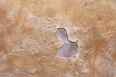 Wall with cracked plaster and dumps — Stock Photo