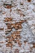 Brick wall with crumbling plaster — Stock Photo