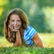 Teenage girl in blue blouse lying on grass — Stock Photo #64410269