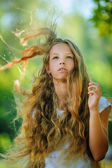 Smiling beautiful teenage wind with flying hair — Stock Photo