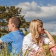 Young couple sits on grass — Stock Photo #64624333