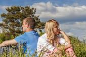 Young couple sits on grass — Stock Photo
