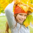 Little girl in sweater with yellow maple leaves — Stock Photo #64706669