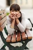 Beautiful girl lays on bench — Stock Photo