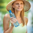 Girl in straw hat drinks water — Stock Photo #67395465
