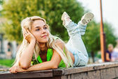 Girl lays on bench — Stock Photo