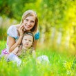 Woman and her little daughter sitting on grass — Stock Photo #69370411