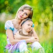Woman and her little daughter sitting on grass — Stock Photo #69370703