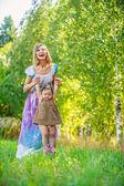 Beautiful young woman plays child field — Stock Photo