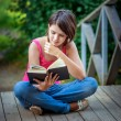 Young beautiful girl sits on bridge and reads book — Stock Photo #69402345