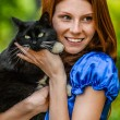 Red-haired smiling young woman with black cat — Stock Photo #69929841