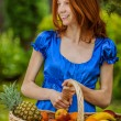Red-haired smiling young woman with a fruit basket — Stock Photo #69926949