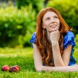 Red-haired smiling young woman lying on grass — Stock Photo #69929531
