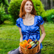 Young woman in sitting on lawn with vegetable basket — Stock Photo #69930103