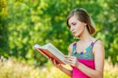 Serious young beautiful woman holding red book — Stock Photo