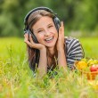 Young woman lying grass headphones fruit — Stock Photo #70170023