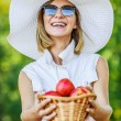 Woman wiht wicker basket holds red apples — Stock Photo #71843881