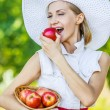 Woman wiht wicker basket holds red apples — Stock Photo #71844089