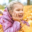 Little girl buried in autumn leaves yellow — Stock Photo #72515831