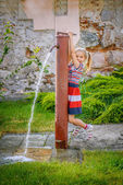 Little girl opens water tap — Stock Photo