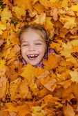 Little girl buried in autumn leaves yellow — Stock Photo