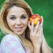 Young woman offering red apple — Stock Photo #77187595