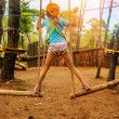 Постер, плакат: Girl climbing in adventure park