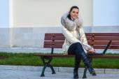 Vrouw in witte jas zittend op de Bank — Stockfoto