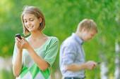 Young woman and man with phone — Stock Photo