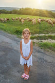 Little girl on pastures with sheep — Stock Photo