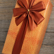Beautifully decorated gift box with bow on wooden — Stock Photo #53488369