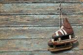 Vintage pair of  ice skates hanging on a cracked paint wall — Stok fotoğraf