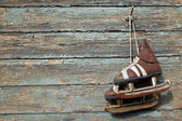 Vintage pair of  ice skates hanging on a cracked paint wall — Stock Photo