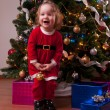 Cute Baby Girl in Santa costume decorating Christmas tree — Stock Photo #56650765