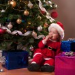 Cute Baby Girl in Santa costume near Christmas tree — Stock Photo #56650769