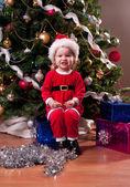 Cute Baby Girl in Santa costume near Christmas tree — Stock Photo