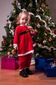 Cute Baby Girl in Santa costume near Christmas tree — Stock Photo