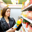 Woman buying a bottle of juice in the store — Stock Photo #73917267